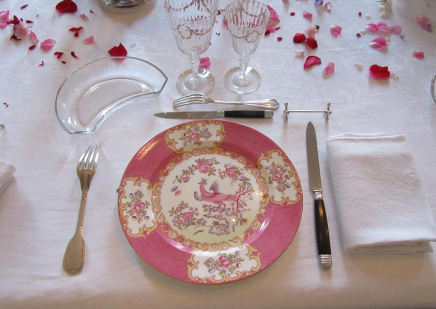 Plate and cuttlery with rose petals in the dining rooom